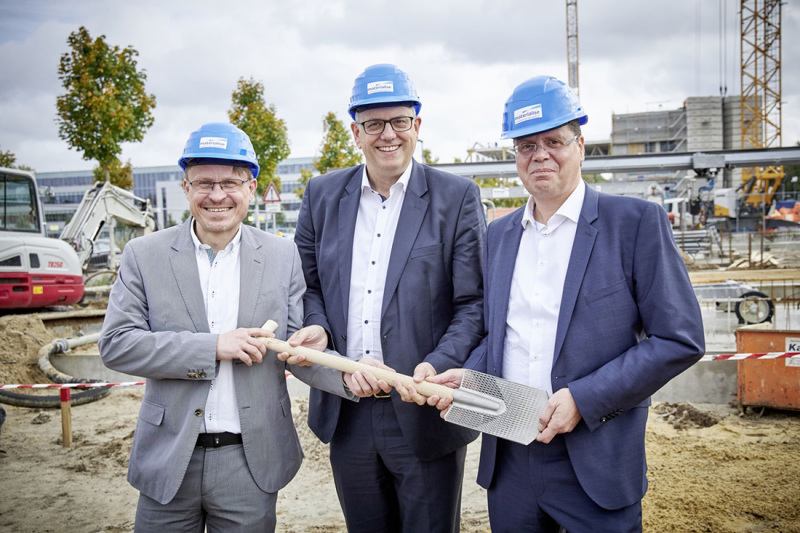 Drei Personen halten eine Schaufel in der Hand. Sie stehen auf einer Baustelle.